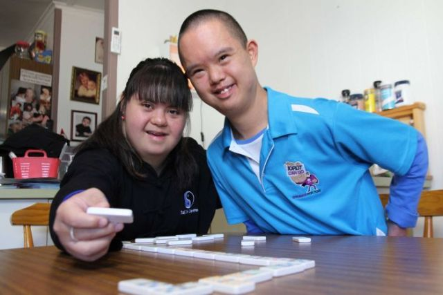 Jess and Jordy sit close together smiling, Jess' arm around Jordy and she is holding a domino piece above their domino game