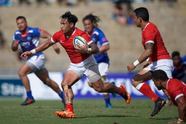 One player holding the ball runs past several other players.