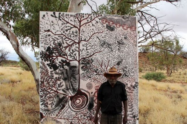 Peter Mungkuri stands beside his painting which is in a tree