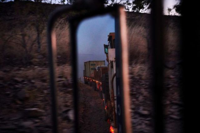 a view of the trucks mirror on dusk showing all three trailers