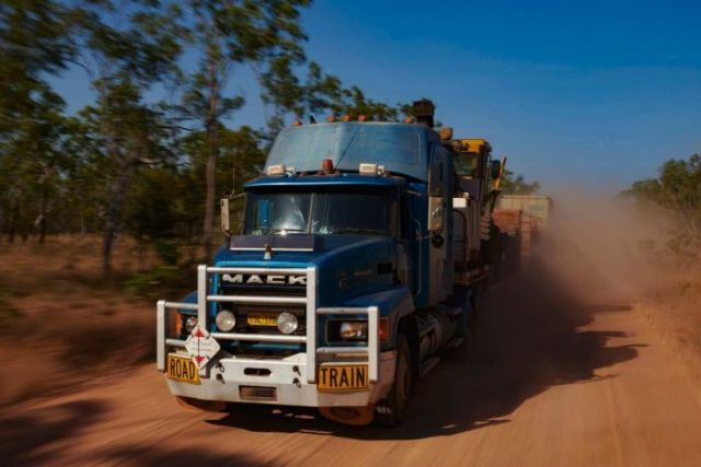 The truck picks up speed over a smoother section of the road