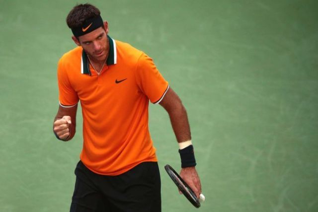 A male tennis player in an orange shirt clenches his fist and looks off to the side
