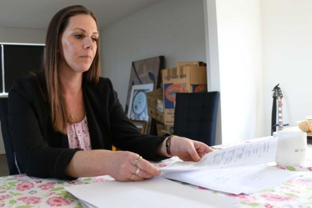 Amanda Dunn examines paperwork related to her late husband's insurance policy