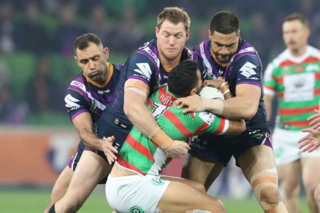 Alex Johnston is tackled by three Melbourne Storm players.