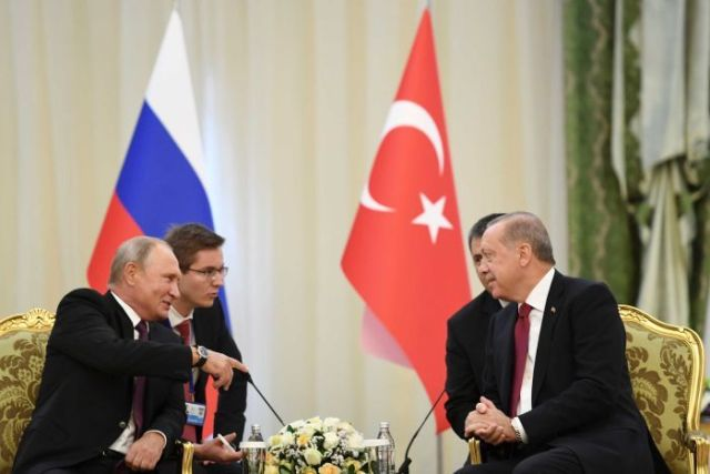 Erdogan and Putin are seen talking at the trilateral summit on Syria in Tehran.