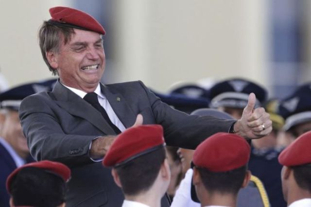 Brazilian politician Jair Bolsonaro in a red berest with young cadets