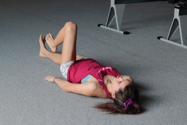 Ella Cummings lying on her back on the floor of a gym flexing her left knee