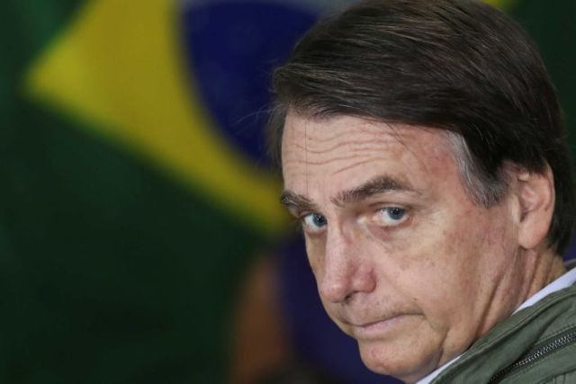 Brazil's new president in front of a flag