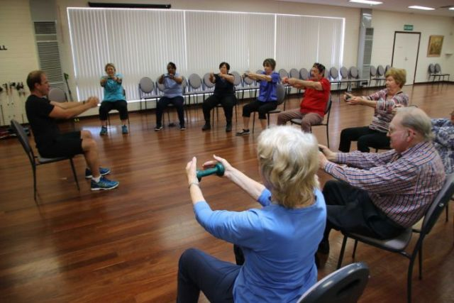 A group of seniors sit in a circle doing arm exercises