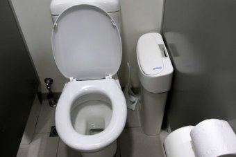 A white toilet with sanitary bin.