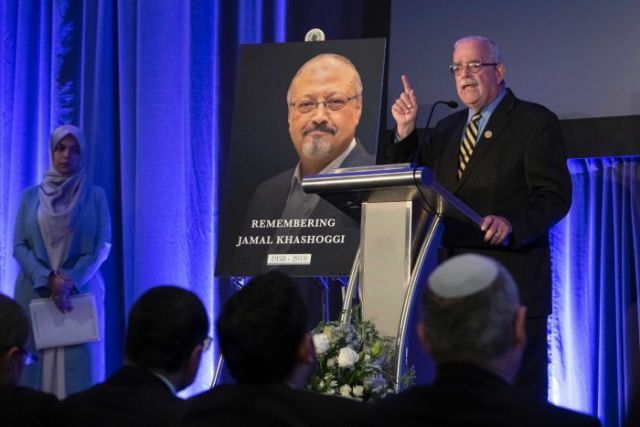 Rep. Gerry Connolly, D-Va stands behind a podium on stage and speaks before a picture of Jamal Khashoggi