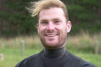 A man wearing a wetsuit looks at the camera