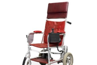A red wheelchair, which is fitted with a joystick and a motor.