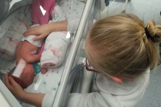 A little girl gently touches her prematurely born sister in a humidicrib.