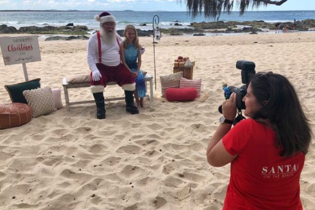Santa on the beach photo being taken.