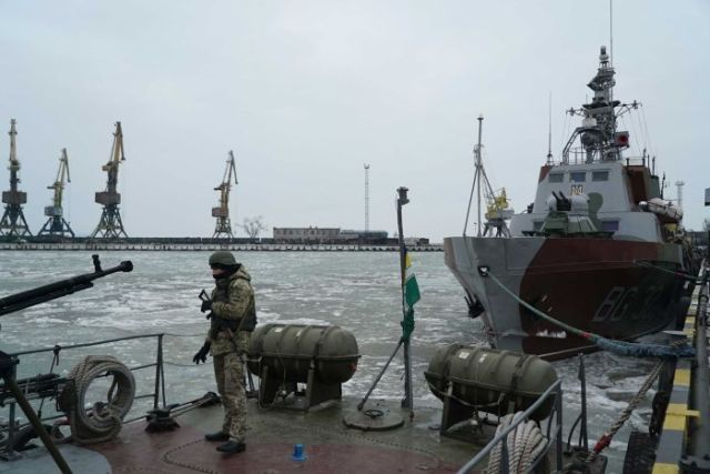 A Ukranian serviceman boards a coast guard ship in icy waters in the Sea of Azov