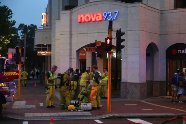 A group of fire fighters standing in front of a  building with Nova 93.7 neon sign