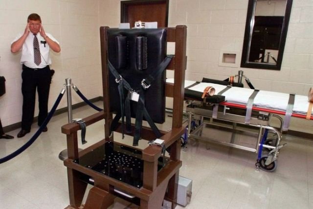 A warden stands next to an electric chair at Riverbend Maximum Security Institution in Nashville, Tennessee in 1999.