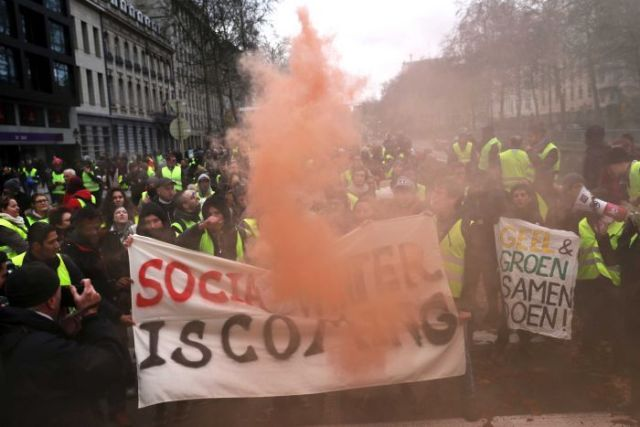 "A large crowd of people in yellow vests gather around a sign that says ""social winter is coming""."