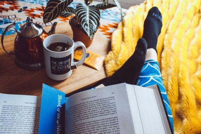 Person drinking tea, reading a book and wearing comfy socks.
