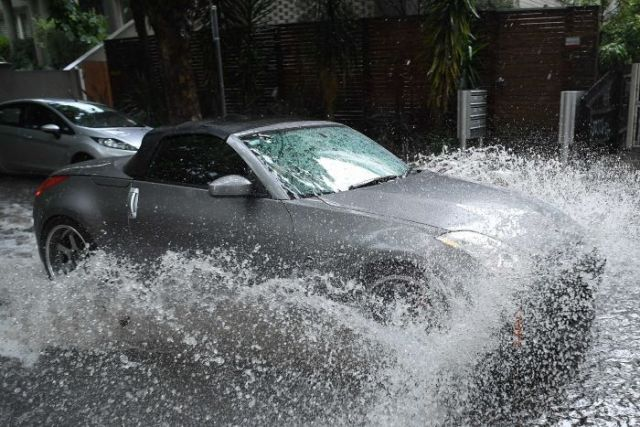 Flood water splashes up around a grey car as it drives down flooded Melbourne street.