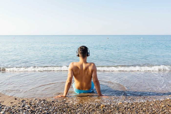 Rear view of a man sitting in the the water at the beach with headphones on.