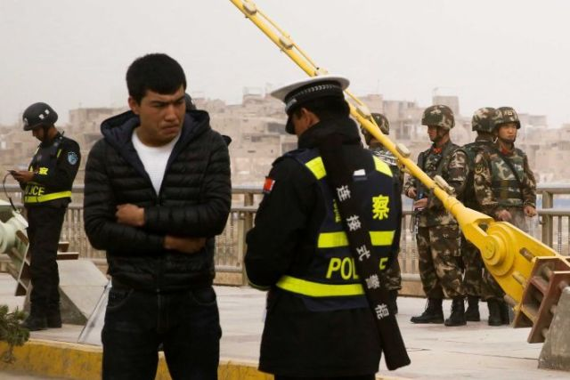 A police officer speaks to a man as security forces keep watch behind them.