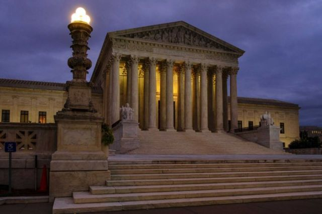 A landscape photograph shows the US Supreme Court shot before sunrise with a moody, overcast purple sky.