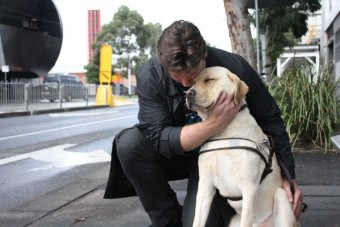 Disability access advocate David Foran kneels with his guide dog, Oliver, at a tram stop in Southbank