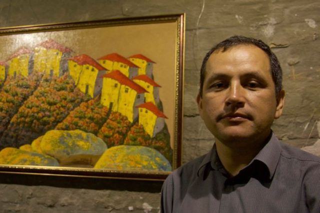 Crimean Tatar Erfan Kudosov stands next to a painting in his art gallery.