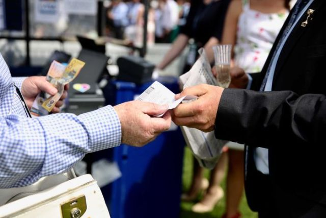 Someone places a bet and hands over cash at the Melbourne Cup.