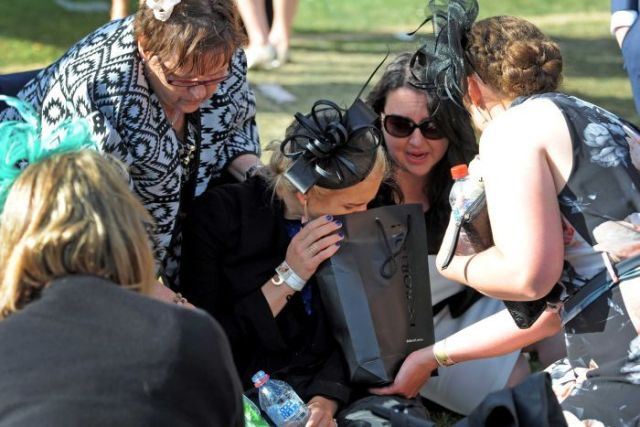 A punter appearing to vomit into bag at the Melbourne Cup.