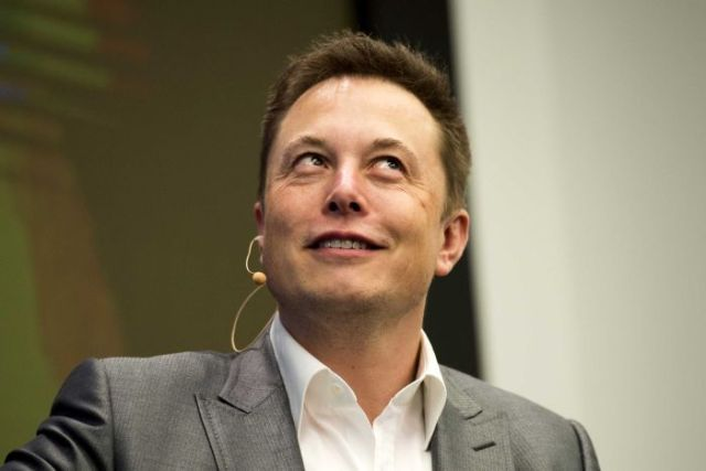 Tesla CEO Elon Musk smiles during a speech at an energy summit.