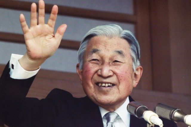 Japan's Emperor Akihito waves to well-wishers from a bullet-proofed balcony of the Imperial Palace in Tokyo.