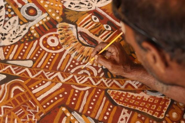 A man paints a huge artwork at Tiwi Arts in the Northern Territory.