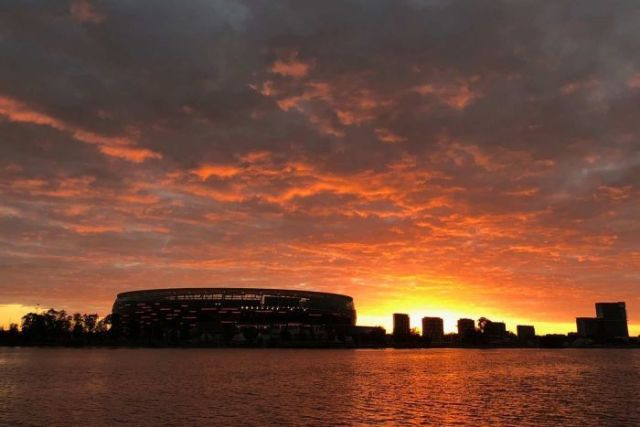 A wide shot showing a glowing red sunrise over Perth Stadium and the surrounding skyline.
