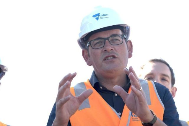 Daniel Andrews, wearing a hard hat and hi-vis vest, speaks at a press conference.