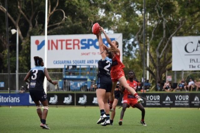 Two female football players jump for the ball in Darwin.