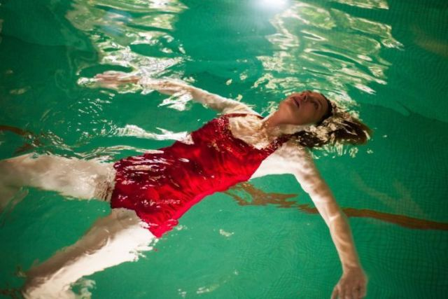 Mid-shot of performer Tiffany Lyndall Knight floating face up in an indoor pool wearing a red swimsuit.