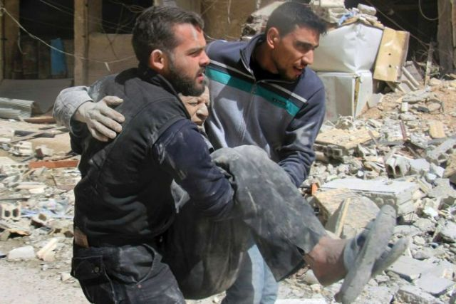 Two men carry and injured man in their arms past rubble.