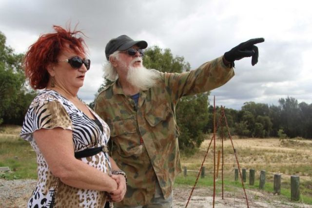 A woman stands in bushland next to a man wearing camouflage clothing who is pointing in the distance.
