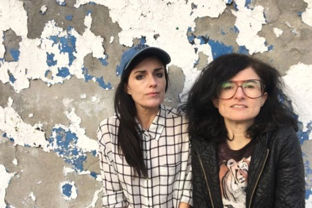 Colour photograph of sisters Dominique and Dan Angeloro of art collective Soda_Jerk standing in front of a distressed wall.
