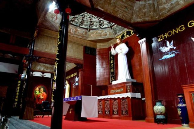 A large statue of Jesus stands inside a building with red carpet and Chinese calligraphy on the walls and pillars