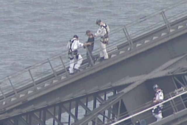 Police escort a man down the slope of the bridge.