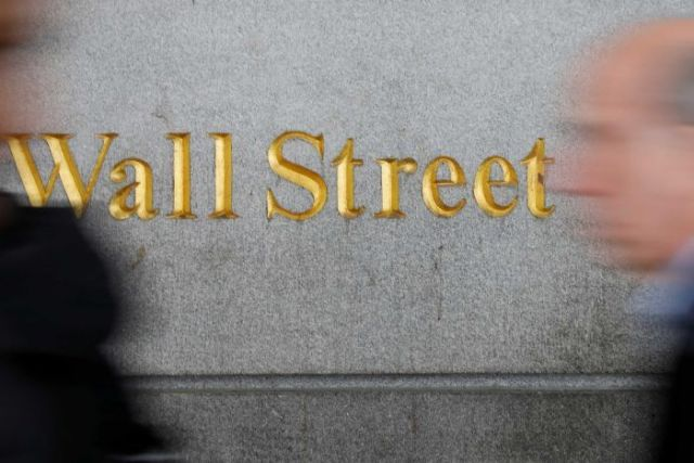 People walk past a Wall Street sign near the New York stock exchange.