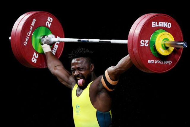 Weightlifter Francois Etoundi pokes out his tongue as he holds weights above his head