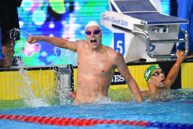 Scotland's Duncan Scott propels himself out of the water to celebrate winning the 100m freestyle