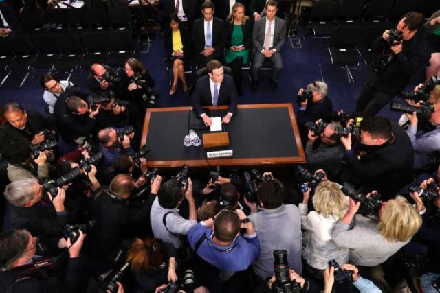 Mark Zuckerberg sits at a desk by himself, surrounded buy photographers.