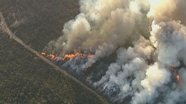 Aerial views show bushfire burning in south-west Sydney