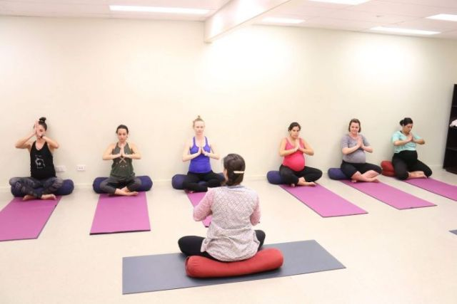 A group of pregnant women sitting on yoga mats in a cross-legged pose.